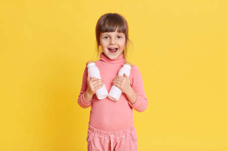 Little beauty girl in pink clothing with brown hair holding two bottles of milk and looking at camera with exited facial expression, keeps mouth opened, kid prefers healthy eating. 免版税图像