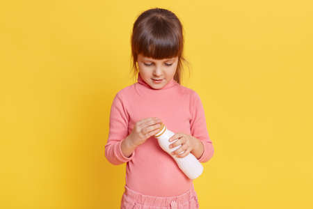 Small girl with ponytail wearing pink shirt with white plastic bottle for dairy products in her hands posing on yellow background, child looking at yogurt and tries to open it.