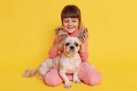 Child with dog playing together, kid lifts ears of puppy and laughing, looks at pet, cute little girl wearing casually, raising Pekingese ears up na d having fun.
