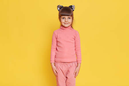 European adorable little female child posing isolated over yellow background, keeps hands at seams, looks at camera with calm expression, wearing pink pants and shirt.