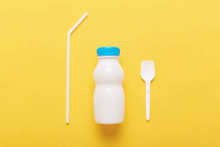Three subjects isolated over yellow background, bottle from milk or yogurt, plastic spoon and straw, using plastics, diary product in white bottle with blue cap.