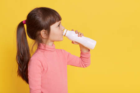 Child drinks milk while posing isolated over yellow background, profile of little dark haired female kid drinking yogurt from bottle, small girl wearing pink clothing, has ponytail, copy space.