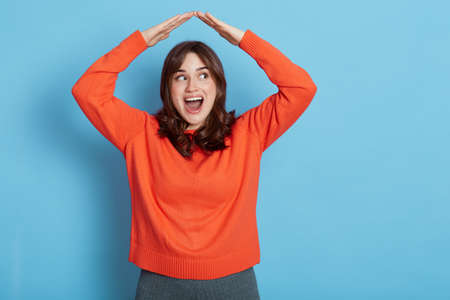 Portrait of happy excited girl wearing orange sweater feeling safe, confident under house roof gesture, dreaming of home, looking aside with opened mouth, posing isolated over blue background.