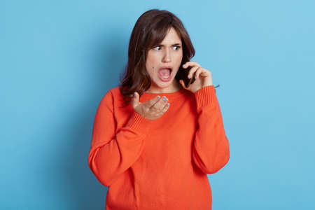 Scared dark haired woman gasps from fear, feels shock from received news, looking aside with widely opened mouth, talks via smart phone, realizes having big problem, wears orange jumper.