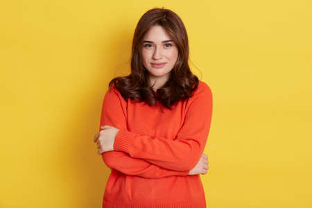 Pretty smiling European woman embraces herself gently, looks at camera, expresses self love, feels comfortable, being in good mood, isolated over yellow background.