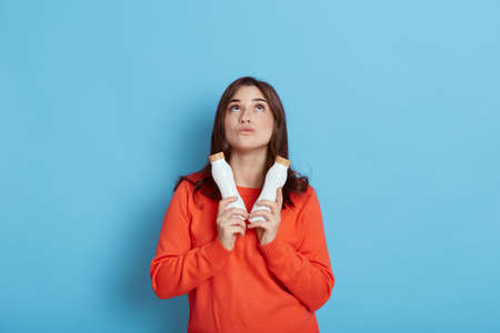 European young and healthy Caucasian woman holding two bottles fresh milk, looking up with pensive facial expression, lady with yogurt wearing casual orange sweater isolated over blue background. 免版税图像