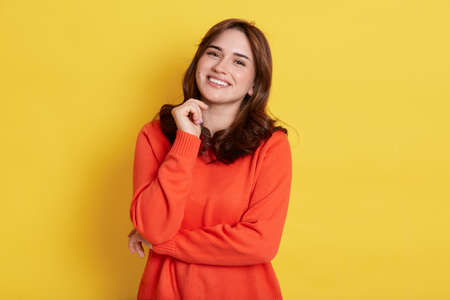 Happy smiling dark haired woman with pleasant appearance, wearing casually, looking at camera with toothy smile, keeping fist under chin, standing isolated over yellow background.