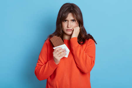 Sad European dark haired female wearing casual attire posing isolated over blue background, looking at camera with upset expression, has toothache, suffering from pain, keeping fist on cheek.