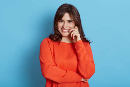 Happy pleasant looking woman with dark hair talking phone, hearing great news, looks at camera with charming smile, wearing casual orange jumper isolated over blue wall, female talking via cell phone.