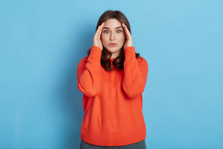 Beautiful woman with dark hair, keeps hands near eyes, wears casual orange jumper, posing isolated on blue background, looks with big eyes at camera, keeping hiding gesture. 免版税图像