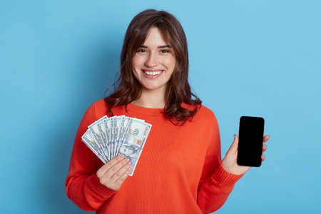 Happy smiling young woman in orange casual clothes, holding mobile phone, holding fan of cash money in dollar banknotes, isolated on blue wall, looks at camera, expressing joy. 免版税图像
