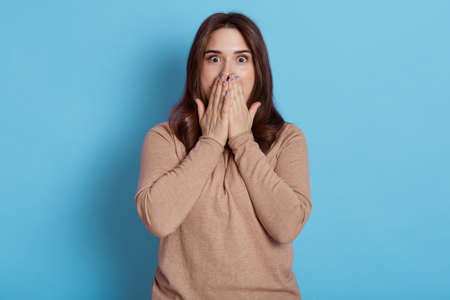 Young European female dresses beige shirt, looking at camera with fear in eyes, covering mouth with palms, looks at camera with big eyes, posing isolated over blue background.