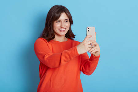 Portrait of young attractive woman making selfie photo with smart phone isolated over blue background, lady looks at device with happy smile, dark haired female has video call. 免版税图像