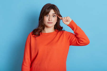 Portrait of dark haired woman in urban style jumper makes stupid sign with finger near head, gesturing bad mind, dumb insane idea, isolated on blue background, female looks at camera with astonishment