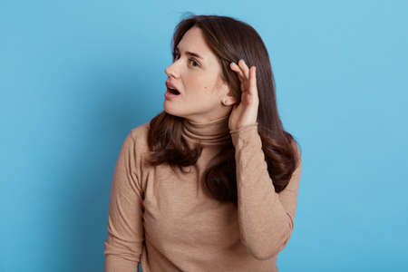 I can't hear you! Confused woman keeping hand near ear to listen better, having hearing problems, difficult to understand, female with curious look looking away, keeps mouth opened, against blue wall.