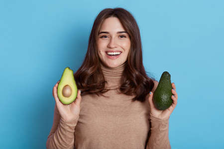 Close up portrait of young dark haired woman with two halves of green fresh avocado posing isolated over blue background, smiling female with dark hair prefers organic food. 免版税图像