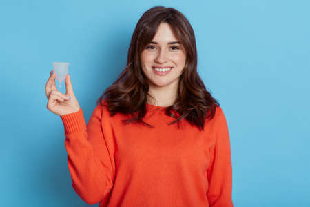 Attractive dark haired female holding in hand plastic menstrual cup isolated over blue background, smiling woman thinks about her personal hygiene product during period, wearing casual orange jumper.