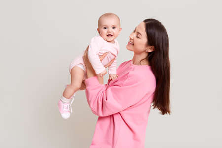 Young cheerful beautiful woman holding baby boy in her hands and looking at her with love, excited toddler girl wearing bodysuit looks at camera, family posing isolated over white background.