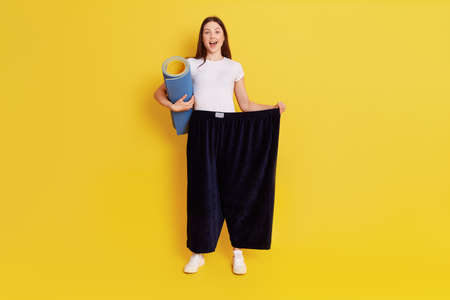 Young European woman in oversize black pants posing isolated over yellow background, holding karemat in hands for doing sports, has excited facial expression, rejoices at achieved result.