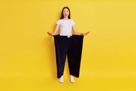 Girl showing weight loss, astonished girl with opened mouth, lady in white t shirt wearing old black pants in huge size, standing isolated over yellow background. 写真素材