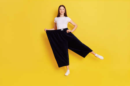 Happy woman after weight loss posing on one hand isolated over yellow background, wearing white casual t shirt and too big black pants, keeps one hand on hip, rejoices at achieved result.