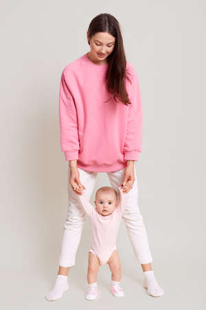 Mother teaching her little baby to walk isolated over white background, dark haired woman wearing white pants and pink sweater holding her toddler with both hands.