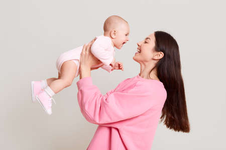 Young European mother holding her baby girl in hands and looking at her baby with love and gentle smile, female with dark hair wearing pink casual sweater playing, with her child. 写真素材