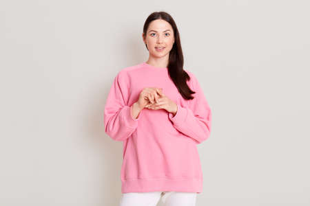 Attractive adorable young girlfriend with dark straight hair and soft healthy skin, dressed in casual pink sweatshirt and white pants, poses against white wall, keeps hands together in front of chest.