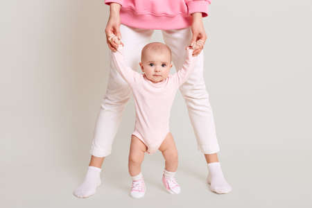 Mom teaches her daughter to walk, faceless female wearing white pants, holding her baby's hands and walking indoor against white wall, kid looks at camera and likes to go.