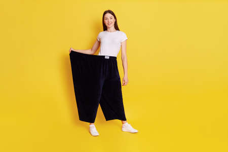 Slim attractive girl with dark hair wearing white caucasian t shirt and too big black pants, female lost weight and being proud of it, looks smiling at camera, isolated over yellow background.
