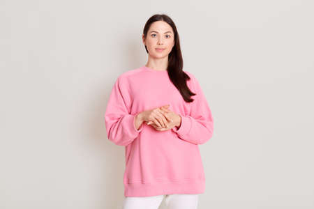 Pretty calm female with dark hair, dressed casual pants and pink sweatshirt, looking with calm expression at camera, keeps hands together in front of chest. Caucasian girl isolated on light background