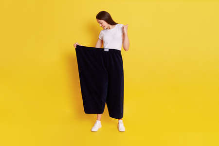 Beautiful dark haired female with perfect body wearing old black pants too big size, lady being glad to loose weight, clenches fist and looks at her trousers, isolated over yellow background. 写真素材