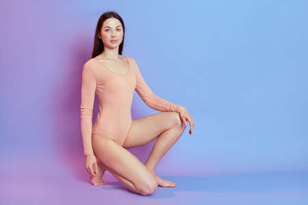 Beautiful girl wearing beige bodysuit with dark hair, has perfect body, sitting on knee, looking at camera with confident expression, isolated on blue wall with pink neon light. 写真素材