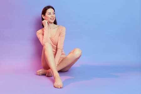 Charming smiling dark haired lady wears beige bodysuit sitting on floor, looking away with smile, copyspace for advertisement, isolated over blue background with pink neon light.