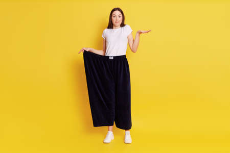 Full length photo of puzzled astonish female wearing too big blag pants, stretching palm aside, looking at camera, being surprised of loosing too much weight, posing isolated over yellow background. 写真素材