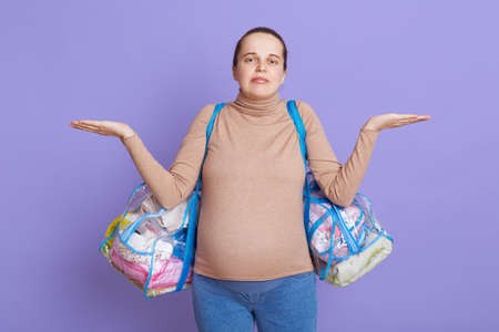 Helpless puzzled pregnant European female with hair bun, wearing casual attire holding bags, don't know where to go to maternity home, posing isolated over lilac background.