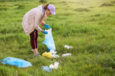 Full length portrait of young female volunteer collecting garbage, woman in casual clothing picking up waste in meadow, land pollution, environmental problem. 写真素材