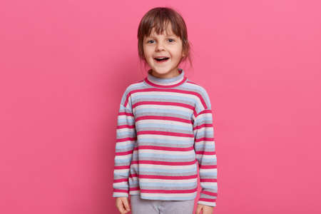 Happy excited preschooler girl wearing casual style striped shirt posing isolated over pink background with satisfied and surprised expression, keeps mouth opened, feels happy, looking at camera.