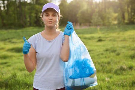 Young Caucasian woman collect garbage out from grasses in garden, helps to save environment, wearing casual attire, looks at camera with tired expression, showing thumb up.