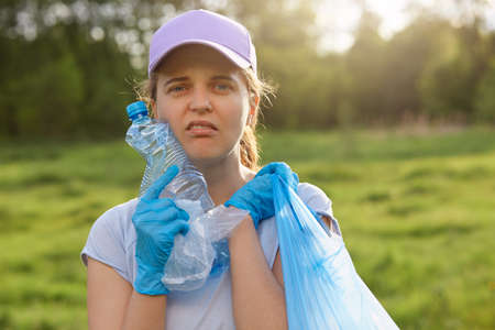 Portrait of young female volunteer posing outdoor, collecting garbage, woman in casual clothing picking up waste in field, land pollution, environmental problem. 写真素材