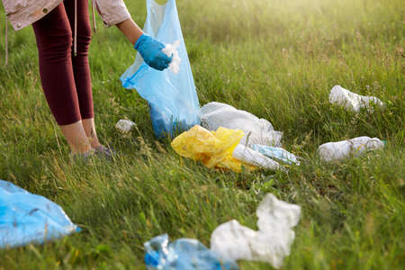Faceless female volunteer wearing leggins and gloves picking up litter in meadow, using blue garbage bag, cares about environment, fights pollution, removes rubbish on the field.