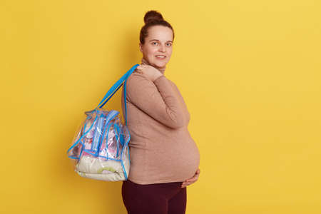 Profile of calm relaxing pregnant female wearing casual turtleneck standing with bags, being ready to go to maternity home, touching belly with hand, isolated over yellow background.