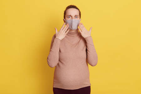 Astonished pregnant female wearing casual attire and medical mask, being scared and shocked, keeping palms near face, hearing bad news, isolated over yellow background. 写真素材