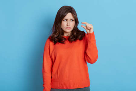 Dark haired female wearing orange sweater showing small size gesture with finger isolated over blue background, has unhappy facial expression, looks at her fingers.