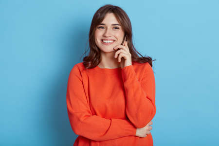 European female with happy facial expression posing with phone near ear, has pleasant conversation, hears excellent news, smiling to camera, dresses in orange jumper, isolated over blue background.