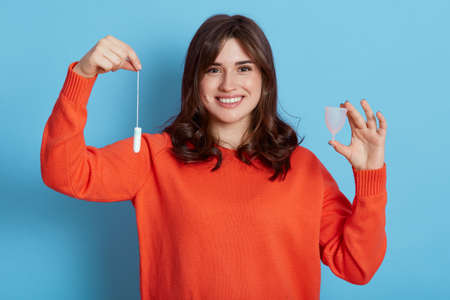 Smiling dark haired woman compares two variants of women hygiene, holding cotton tampon and menstrual cup in hands, looks smiling at camera, isolated over blue background.