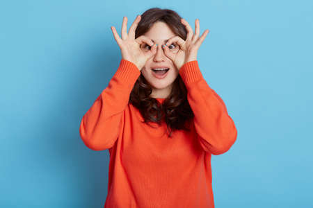 Funny young adult female wearing orange sweater showing binoculars gesture with both hands. cover eyes with fingers as spy, looks at camera with smile, isolated over blue backgraund.