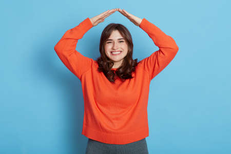 Smiling dark haired girl wearing casual style outfit making roof from her head and looking at camera with pleasant smile, wants to be in safety, isolated over blue background.