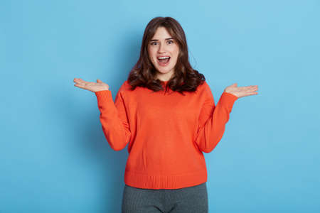 Pleasant looking female in casual style outfit posing with spreading hands aside and looking at camera with opened mouth and astonish facial expression, being a bit confused. Stockfoto
