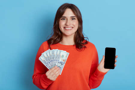 Happy woman with fan of banknotes and phone in hands looking directly at camera with satisfied expression, dark haired lady wins big sum of money, isolated over blue background. Stockfoto